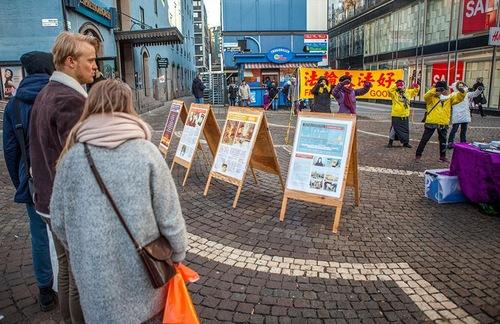 Практикуючі Фалунь Дафа провели захід на Сінній площі в Стокгольмі. Перехожі розглядають плакати і спостерігають за демонстрацією вправ