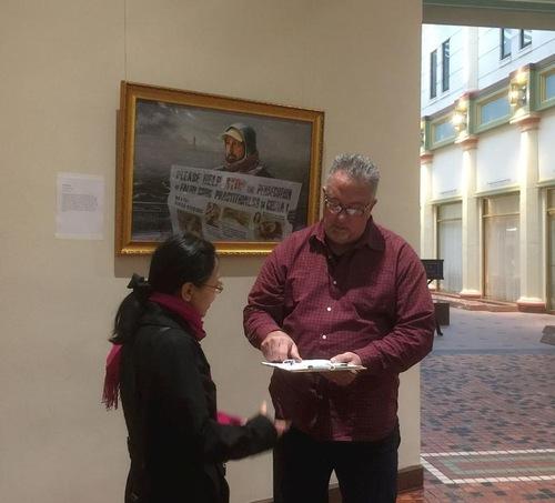 Відвідувачі підписують петицію, щоб засудити насильницьке вилучення органів у живих людей