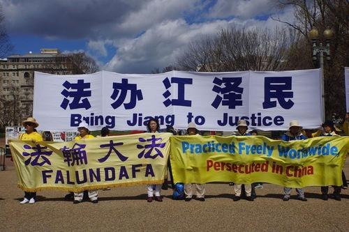 Практикуючі Фалуньгун тримають плакати с закликом припинити переслідування у Китаї та залучити Цзян Цземіня до правосуддя
