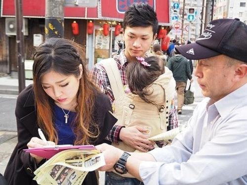 Молоде подружжя підписує петицію, щоб підтримати мирний протест практикуючих Фалуньгун проти переслідування в Китаї (Йокогама, Японія)
