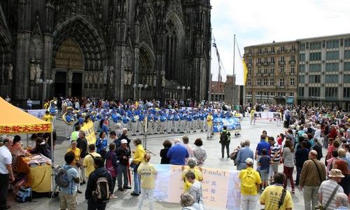 Духовий оркестр Тянь Го практикуючих Фалуньгун (система цігун) виступає перед Кельнським собором до початку маршу