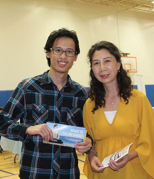 У (зліва) дізнається від практикуючої про Фалунь Дафа