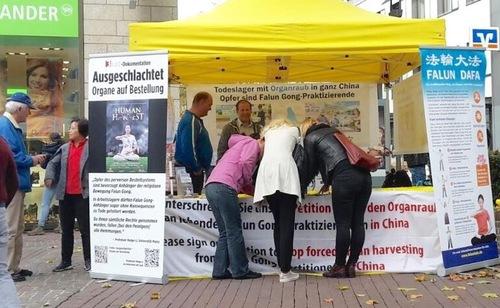 Люди підписують петицію в інформаційному наметі Фалунь Дафа, Ульм, 21 жовтня 2017 року