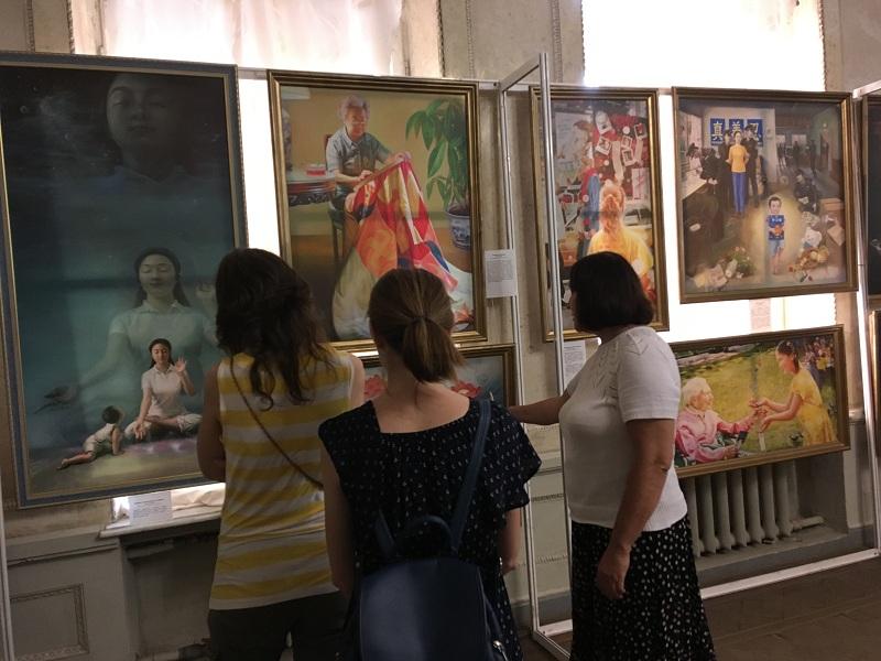 Екскурсовод за допомогою картин розповідає глядачам про систему самовдосконалення Фалунь Дафа і  про репресії її прихильників в Китаї