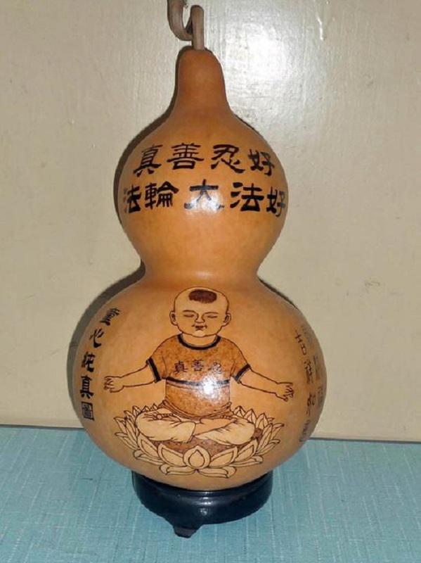 Гарбузовий глечик з написом вгорі «Фалунь Дафа несе добро. Істина, Доброта, Терпіння — праведні принципи»