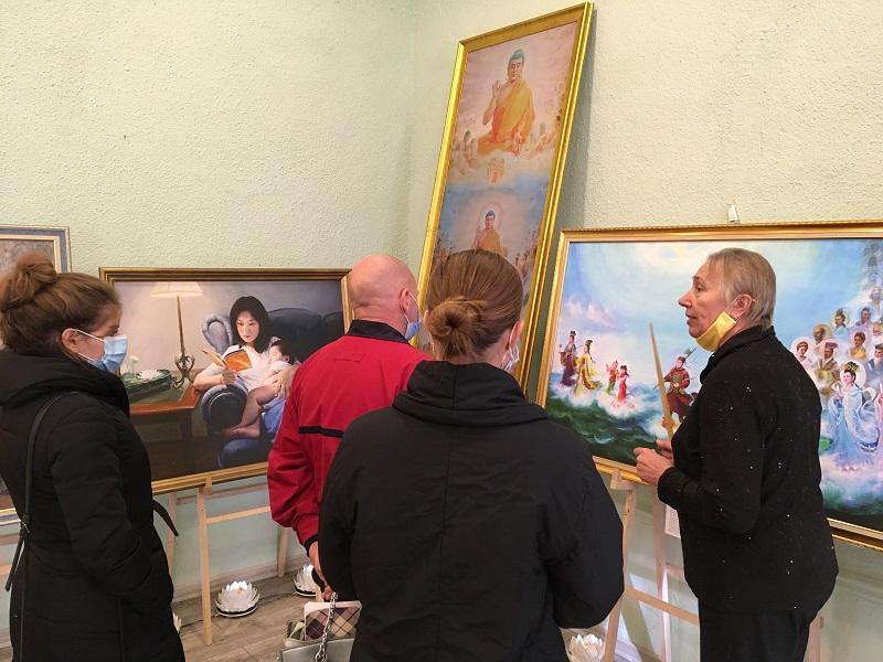 Екскурсоводи розповідають відвідувачам на виставці зміст картин