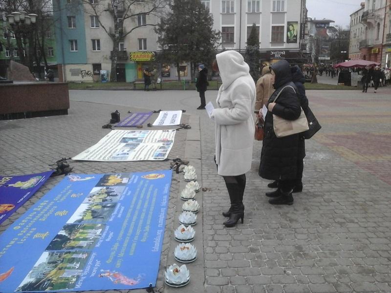 Глядачі читають плакати про практику Фалуньгун і про репресії у Китаї її послідовників з боку комуністичного режиму (Фото: Fofg.in.ua)