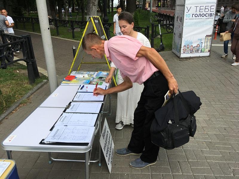 Люди підписують петицію «Покладемо край злій комуністичній партії Китаю» (Фото: Fofg.in.ua)